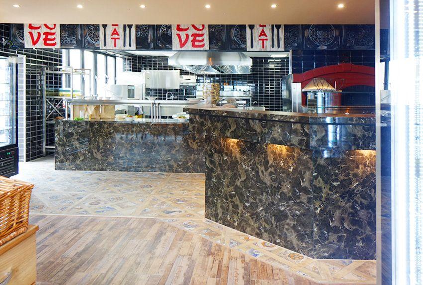 Einsehbare Küchenbereiche und zum Speisenangebot passende Motive auf den Wachstuch-Tischdecken als besondere Attraktionen in der Gastronomie